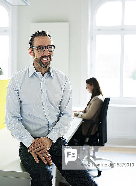 Happy businessman in office with employee in background