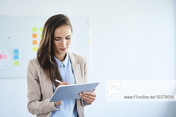 Junge Geschäftsfrau schreibt im Büro auf Tablett
