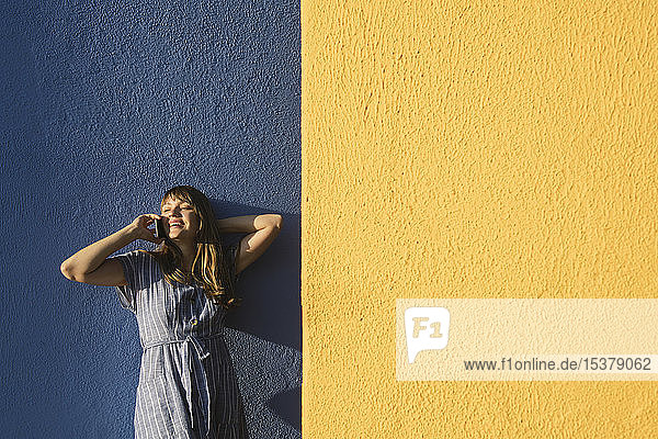 Glückliche Frau am Telefon vor gelben und blauen Wänden
