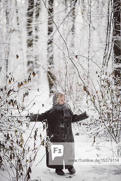 Little girl wearing coat standing in winter forest