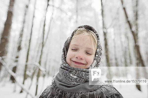 Portrait of happy little girl wearing headscarf in winter forest