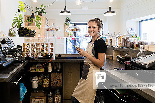 Portrait of smiling young woman with cell phone behind the counter in a cafe