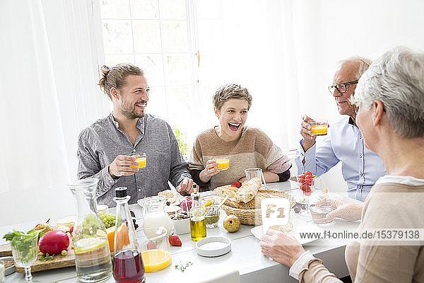 Glückliches älteres Ehepaar mit erwachsenen Kindern beim Mittagessen zu Hause