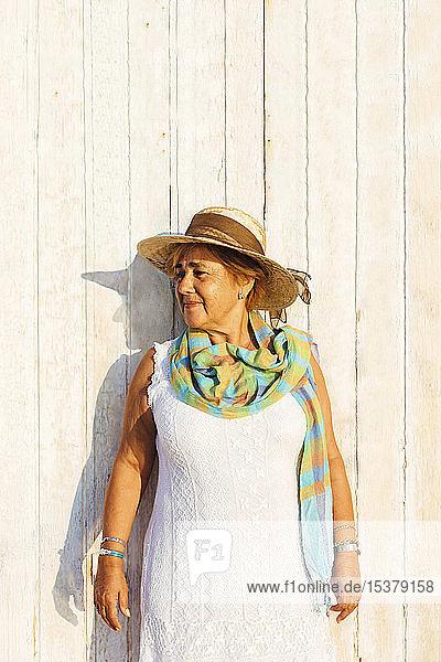 Porträt einer älteren Frau mit Hut an einer Holzwand