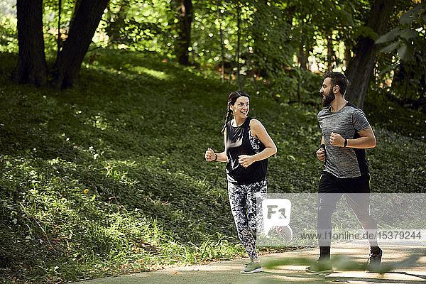 Sportliches Paar läuft auf Waldweg
