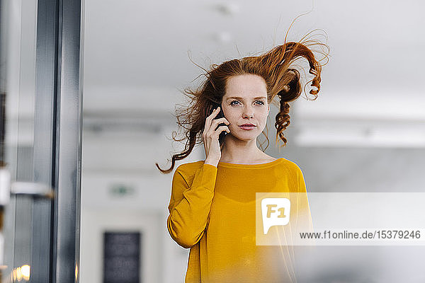 Woman with windswept hair on the phone in office
