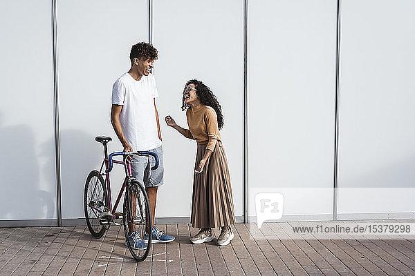 Glückliches Paar mit Fahrrad vor weißem Zaun stehend  lachend Glückliches Paar mit Fahrrad vor weißem Zaun stehend, lachend