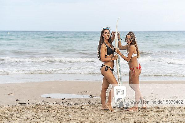 Porträt von zwei Freundinnen  die mit einem Surfbrett am Strand stehen