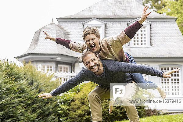 Glückliches Paar amüsiert sich im Garten seines Hauses