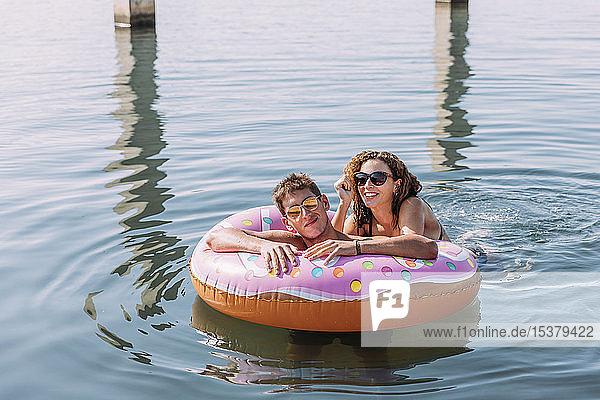 Junges Paar badet im Meer auf einem aufblasbaren Schwimmer in Donutform