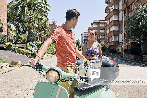 Young couple standing at vintage motor scooter outdoors