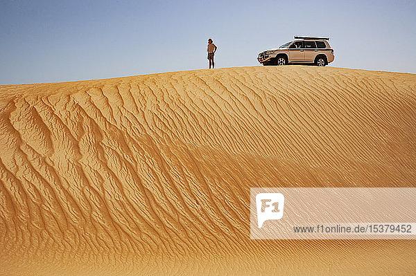 Mann steht in der Wüste  neben Geländewagen  Wahiba Sands  Oman