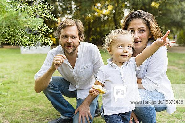 Eltern mit einer kleinen Tochter  die mit dem Finger auf eine Wiese zeigt
