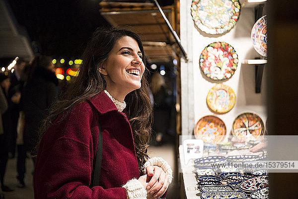 Porträt einer lachenden jungen Frau auf dem Weihnachtsmarkt