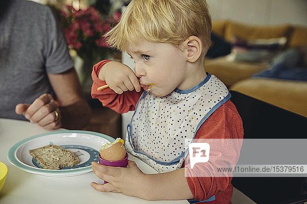 Blond little boy eating breakfast egg