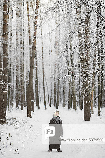 Smiling little girl standing in front of winter forest