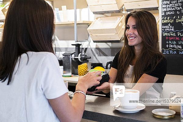 Kunde bezahlt bargeldlos mit Smartphone in einem Cafe