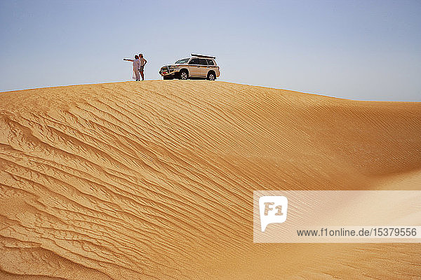 Tourist steht auf Düne neben Geländewagen mit seinem Fahrer  Wahiba Sands  Oman