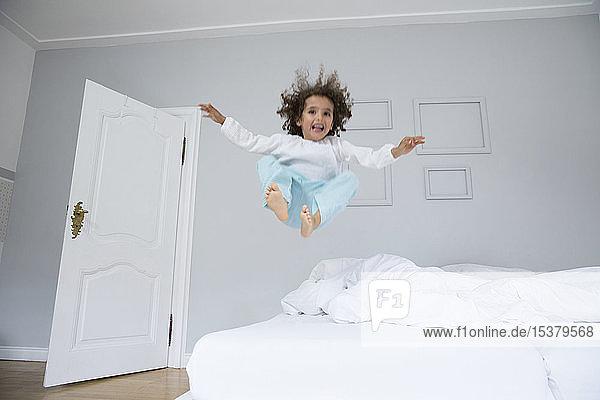 Verspielter Junge hüpft im Bett
