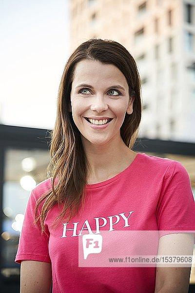 Porträt einer glücklichen Frau mit rosa T-Shirt in der Stadt