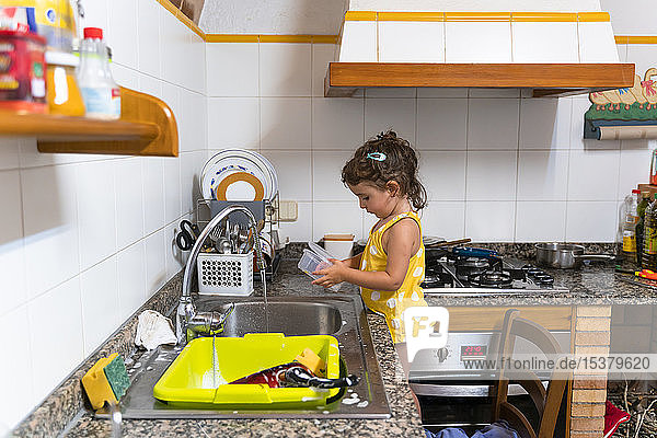 Little girl washing dishes in the kitchen at home