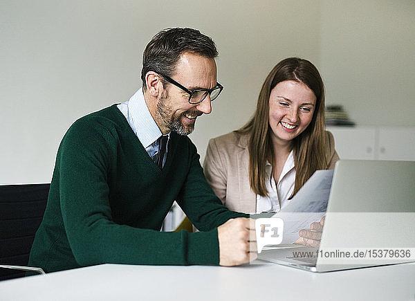 Lächelnder Geschäftsmann und Angestellter mit Laptop und Dokumenten am Schreibtisch im Büro