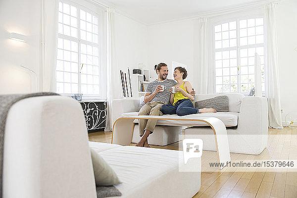 Glückliches junges Paar sitzt zu Hause auf dem Sofa