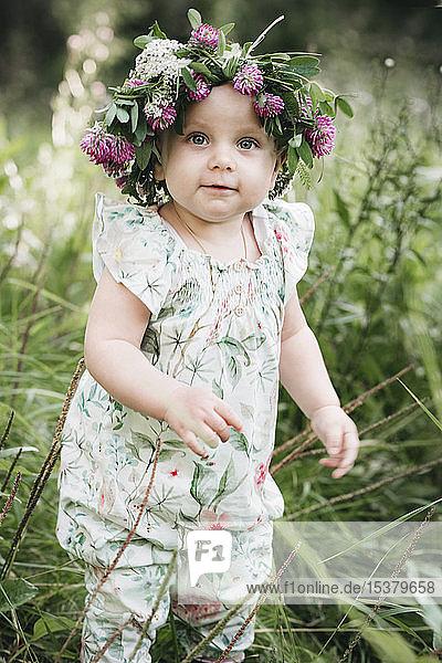 Porträt eines niedlichen kleinen Mädchens mit Blumenkranz auf dem Kopf