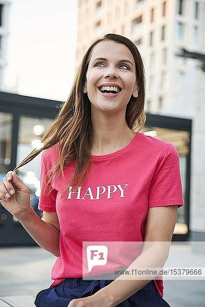 Porträt einer lachenden Frau mit rosa T-Shirt in der Stadt