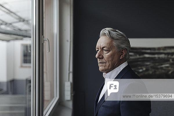 Leitender Geschäftsmann schaut aus dem Fenster
