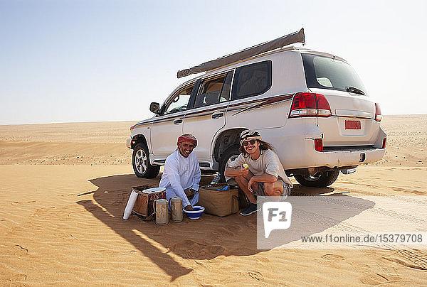 Tourist bei einer Kaffeepause mit seinem örtlichen Fahrer in der Wüste  Wahiba Sands  Oman
