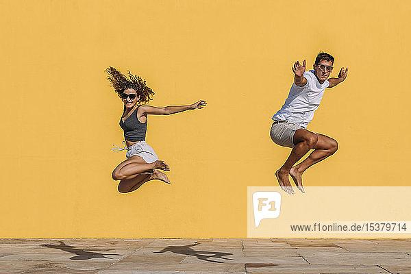 Junges Paar springt vor eine gelbe Mauer