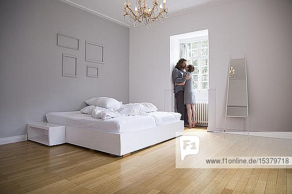 Junges Paar umarmt und küsst sich zu Hause am Fenster im Schlafzimmer
