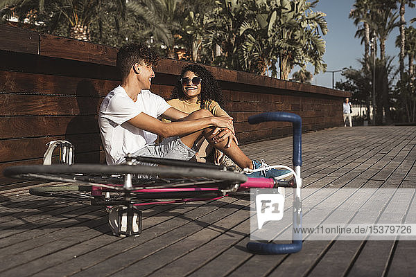Junges Paar mit Fahrrad sitzt in der Stadt und unterhält sich