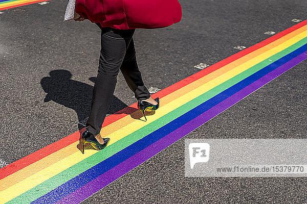 Beine einer Geschäftsfrau  die auf LGBT-Streifen die Straße überquert  London  UK