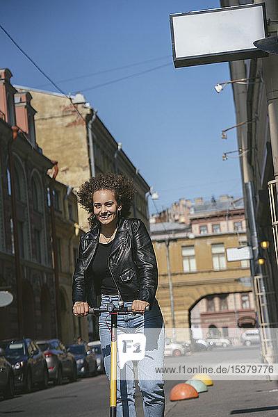 Porträt eines lächelnden Teenager-Mädchens auf einem Roller in der Stadt