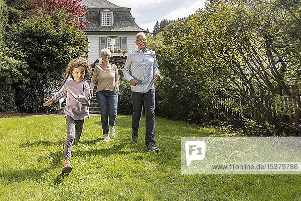 Glücklicher Enkel mit im Garten laufenden Großeltern