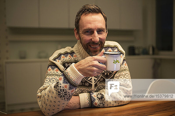 Portrait of happy casual businessman with mug sitting at table at home