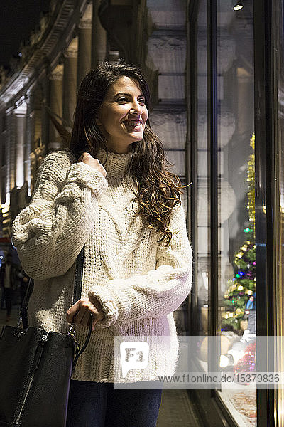Porträt einer glücklichen jungen Frau in einem Strickpullover  die zur Weihnachtszeit ins Schaufenster schaut