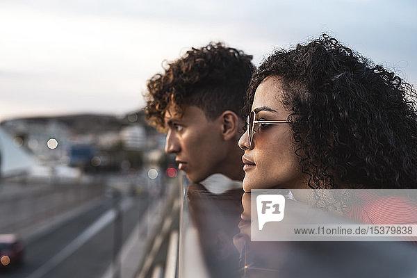 Junges Paar auf der Brücke  Kinn auf dem Geländer ruhend Junges Paar auf der Brücke, Kinn auf dem Geländer ruhend