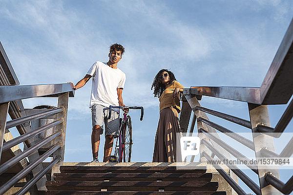 Junges Paar mit Fahrrad,  stehend auf einer Treppe