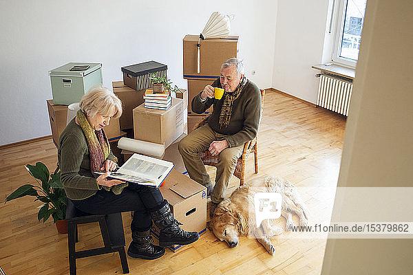 Älteres Ehepaar macht eine Pause  umgeben von Pappkartons in einem leeren Raum