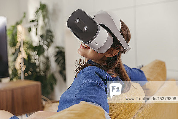 Young woman using VR glasses at home