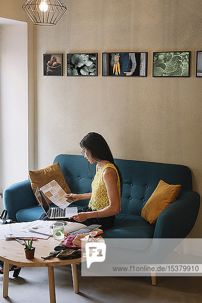 Fashion designer sitting on couch checking color samples