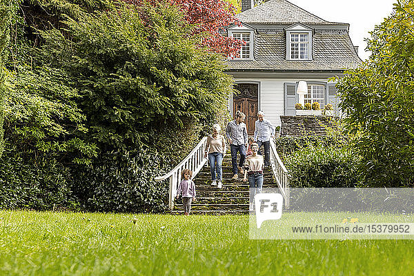 Großfamilie  die auf einer Treppe im Garten ihres Hauses geht
