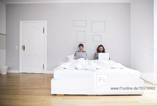 Junges Paar benutzt zu Hause Laptops im Bett