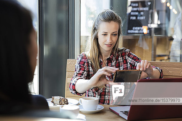 Woman using cell phone and laptop in a cafe