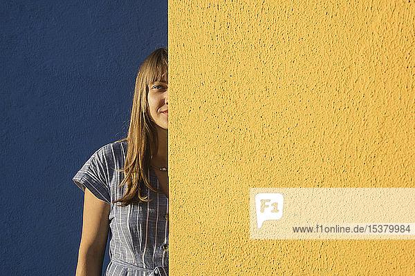 Porträt einer Frau zwischen gelben und blauen Wänden