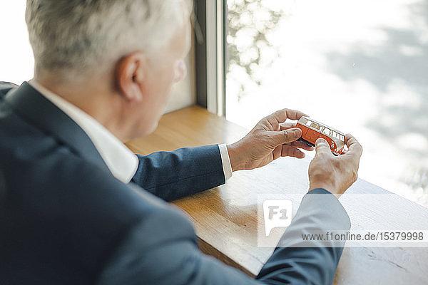 Senior businessman holding minibus model in a cafe