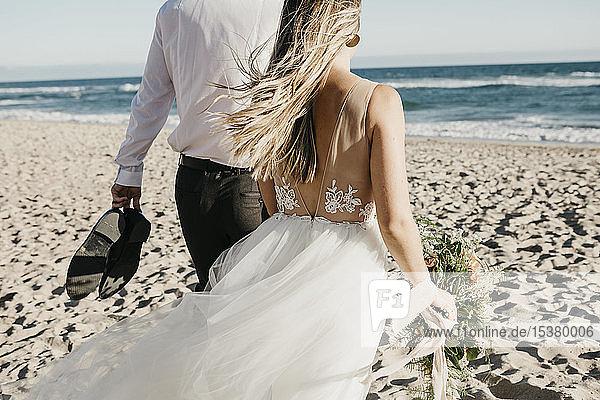 Rückansicht von Braut und Bräutigam beim Spaziergang am Strand